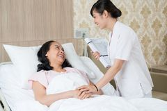 Helping hands. Image of a patient and a nurse talking in the hospital chamber Royalty Free Stock Image