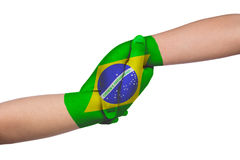 Helping hands of two children with Brazil flag painted. In isolated white background Royalty Free Stock Images