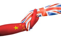 Helping hands of United Kingdom and China. With flags painted on child`s hands in isolated white background Stock Photography