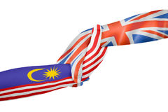 Helping hands of United Kingdom and Malaysia. With flags painted on child`s hands in isolated white background Royalty Free Stock Photography