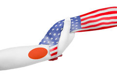 Helping hands of United States of America and Japan. With flags painted on child`s hands in isolated white background Royalty Free Stock Photo