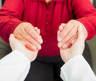 Helping hands. Young carer giving helping hands for elderly woman stock image