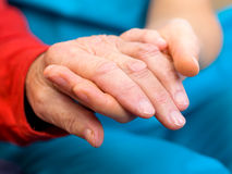 Helping hands. Young carer giving helping hands for elderly woman royalty free stock photography