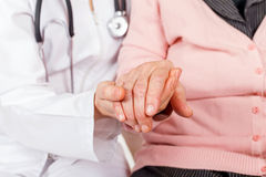 Helping hands. Young doctor giving helping hands for elderly woman stock photography
