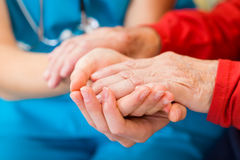Helping hands. Young doctor giving helping hands for elderly woman stock image