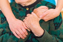 Helping hands. Young doctor giving helping hands for elderly woman royalty free stock images