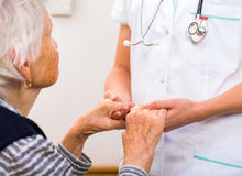Helping hands. Young doctor giving helping hands for elderly woman royalty free stock photo