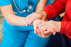 Helping hands. Young doctor giving helping hands for elderly woman royalty free stock photography