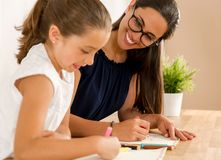 Helping with homework. Young mother helping her daughter with homework at home royalty free stock photos