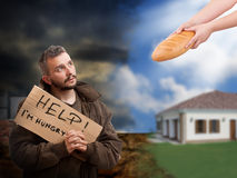 Helping the hungry beggar. Hands give a bread from the hungry beggar royalty free stock photography