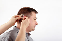 Helping in inserting hearing aid Stock Photos