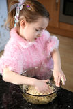 Helping in the kitchen. Young girl mixing food ingredients into a bowl with her hands Stock Images