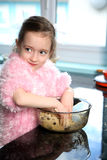Helping in the kitchen. Young girl mixing food ingredients in a bowl with her hands Royalty Free Stock Image
