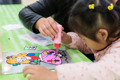 Helping little girl  to draw Stock Photography