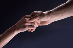 Helping male hand holds hand of a woman Royalty Free Stock Photos