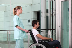 Helping man in wheelchair royalty free stock photo