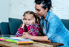 Helping mother and bored daughter doing homework together royalty free stock photos