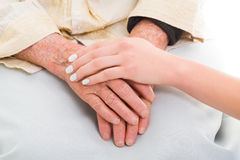 Helping the needy. Elderly hands held by a young person - helping concept Stock Images