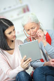 Helping old woman use tablet computer Royalty Free Stock Photo