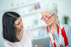 Helping old woman use tablet computer Stock Images