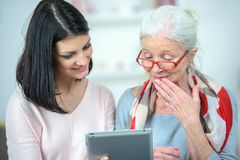 Helping old woman use tablet computer. Helping old women use a tablet computer Royalty Free Stock Image