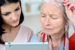 Helping old woman use tablet computer stock photos