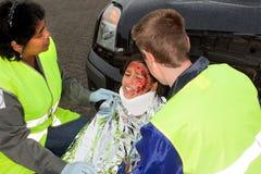 Helping paramedics. Paramedics helping a young injured victim of a car accident stock photography