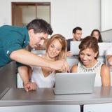 Helping professor. Professor explaining class on the laptop stock image