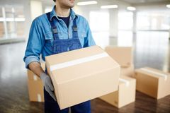 Helping with relocation. Gloved worker in uniform carrying packed box with supplies while doing his work during relocation Royalty Free Stock Photography