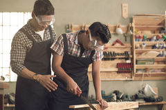 Helping with sawing. Asian men teaching his son how to saw the wooden plank Stock Photography