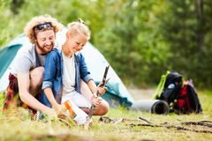 Helping son. Young men and his son sharpening sticks with axe while going to prepare food on campfire Royalty Free Stock Image