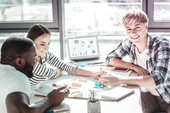 Positive delighted man looking straight at camera. Helping them. Attentive colleagues leaning arms on table and bowing head while discussing their project work royalty free stock photos