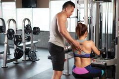 Helping to client. Rear view of fitness trainer helping female client to perform exercise Royalty Free Stock Image