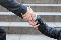 Helping to get up concept. Helping to get up, close-up hands of incognito men helping women in black jacket to get up over grey stone stairs background Royalty Free Stock Photo