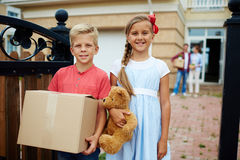 Helping to relocate. Sister and brother helping their parents to carry things while moving for new house royalty free stock photo