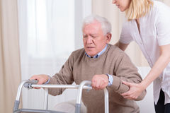 Helping to stand up. Careful nurse helping senior men with walker to stand up Stock Photo