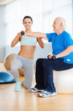 Helping to stay healthy. Confident female personal trainer helping senior men with weight exercise Stock Photo
