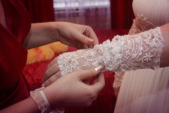 Helping to wear a wedding glove. A young women helps to wear a white lace glove Royalty Free Stock Photos