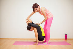 Helping with a yoga pose Royalty Free Stock Photos