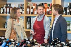 Helpingcouple del sommelier per scegliere vino in negozio fotografia stock libera da diritti