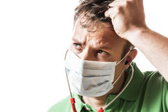 Helpless, anxious and perspiring doctor. In a green shirt with a red stethoscope and surgical mask Royalty Free Stock Photos