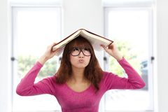 Helpless asian young woman. Holding a book Royalty Free Stock Photos