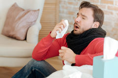 Helpless bearded man suffering from sickness at home Royalty Free Stock Image