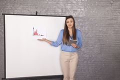 Helpless business woman trying to explain a graph, smiling face stock photography