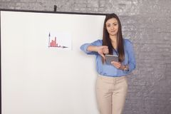 Helpless business woman trying to explain a graph, thumb down stock image
