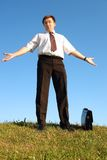 Helpless businessman. Businessman in white shirt and tie standing astride in grass field against clear blue sky spreading helplessly arms Stock Images