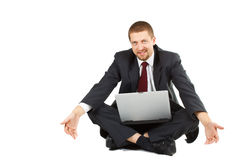Helpless businessman with laptop in his lap. A young businessman in suit and tie sitting crossed legs, laptop in his lap, looking helpless with an uncomfortable Stock Photography