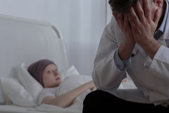 Helpless doctor with his patient. Helpless doctor is sitting next to his patient Royalty Free Stock Images
