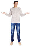 Helpless guy. Full length portrait of confused young man in glasses and beige sweater making helpless gesture isolated on white background Royalty Free Stock Images