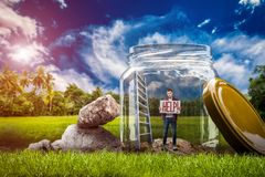 Helpless man with help sign standing in big glass. Fear of loneliness concept, young helpless man with help sign standing in a big glass jar on the green meadow Stock Photo